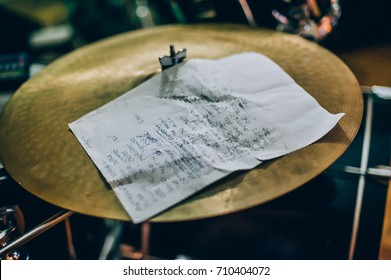 Closeup of lyrics paper with a song text lying on drum set. Musician equipment detail