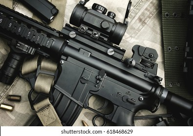 Close-up of a M4A1 weapons and military equipment for army, Assault rifle gun and pistol on camouflage background.