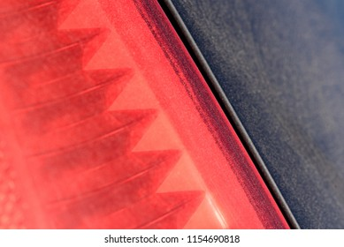 Closeup macro of a dusty rear car brakelight with distinctive plastic patterns and shapes on the vehicles lamp system