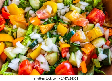 Closeup macro of fresh raw chopped vegetable salad with greens yellow bell peppers on romaine lettuce