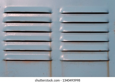 Closeup macro image of a green ventilation air intake grill on green metal