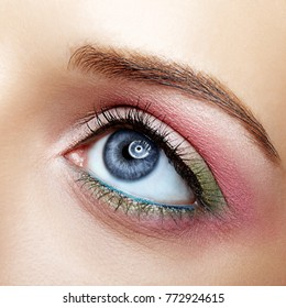 Closeup macro image of human female eye with pink and green makeup