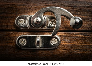 A close-up or macro of metal silver-color sliding lock clasp of a brown textured wood box in horizontal image format.