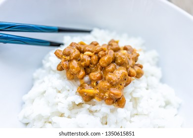 Closeup macro of pair of chopsticks on Asian Japanese natto fermented soy dish meal sticky slimy texture in plain white steamed rice in bowl