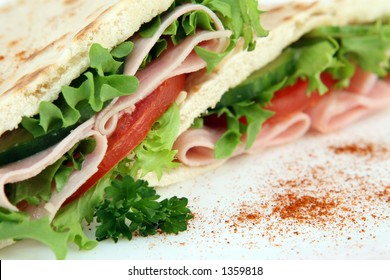 A closeup macro photo of a colorful sandwich with a shallow DOF on white