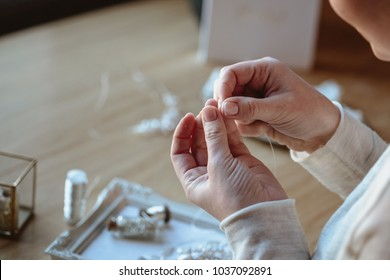 Closeup macro photo of details, workplace of decorator and creator of wedding imitation jewelry. Woman's hands in a process of creation.