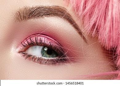 Closeup Macro of Pink Fashion Eye Make-up. Expressive Makeup, Bright Summer Eyeshadows and Magenta Color Hair, Shiny Skin