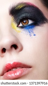 Close-up macro portrait of beautiful woman face make up. Female eye with unusual artistic painting makeup and red lips