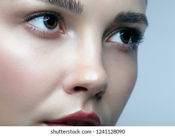 Closeup macro portrait of female face. Woman with natural beauty makeup. Girl with perfect skin on gray background