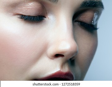 Closeup macro portrait of female face with eyes closed. Woman with natural beauty makeup. Girl with perfect skin on gray background