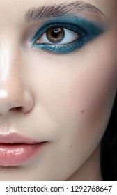 Closeup macro portrait of female face. Human woman half-face  with evening beauty makeup. Girl with perfect skin and blue-green eye shadows