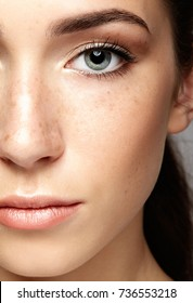 Closeup macro portrait of female face. Human woman half-face  with day beauty makeup. Girl with perfect skin and freckles.