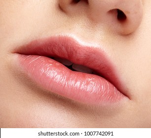 Closeup macro portrait of female part of face. Human woman lips with day beauty makeup. Girl with perfect chubby lips shape.