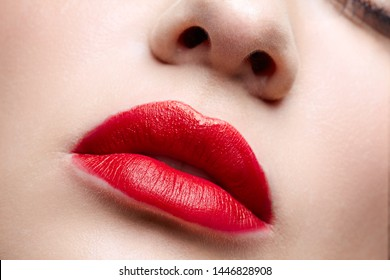 Closeup macro portrait of female part of face. Human woman red lips with day beauty makeup. Girl with perfect lips shape.