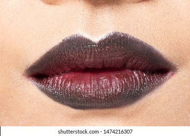 Closeup macro portrait of woman dark deep purple lip teeth, Young female open close mouth. Body Part of Fashion make up express emotion shape Lips with color Lipstick, studio lighting