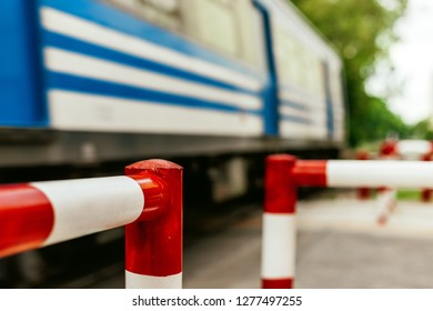 Close-up macro of railway crossing pedestrian fence with train passing quickly