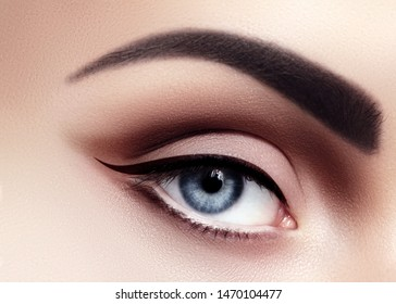 Closeup Macro of Sexy Woman Eyes with Evening Fashion Make-up. Black Liner and Strong Brows. Retro Diva Style Eye Makeup. Cinematic Look