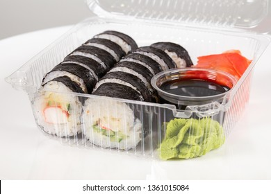 Closeup macro shoot of set of cheap sushi in plastic container isolated on white background. Meal delivery concept. Horizontal color photography.