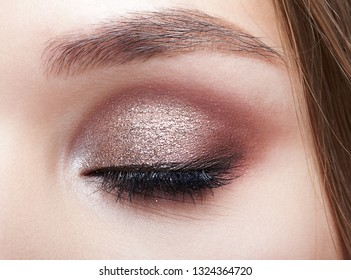 Closeup macro shot of closed human woman eye. Female with smoky eyes makeup