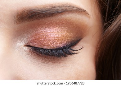 Closeup macro shot of closed human female eye. Woman with natural evening vogue face beauty makeup. Girl with perfect skin and  pink  eyes shadows.