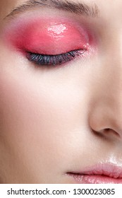 Closeup macro shot of female face and pink smoky eyes beauty makeup. Woman with glossy glitter white skin.