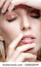 Closeup macro shot of female face and eyes beauty makeup. Woman with glossy glitter white skin. Girl with hand near face and closed eyes.