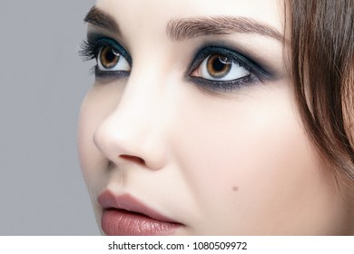 Closeup macro shot of  human female face. Woman with natural evening vogue face beauty makeup. Girl with perfect skin and aquamarine eyes shadows