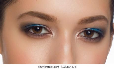 Closeup macro shot of human female eye. Woman with natural evening vogue face beauty makeup. Girl with perfect skin and aquamarine eyes shadows