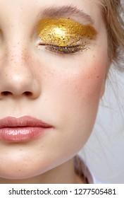 Closeup macro shot of  human female half face with closed eye. Woman with unusual glitter glitzy vogue face beauty makeup. Girl with perfect skin and yellow smoky eyes eye shadows
