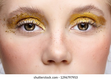 Closeup macro shot of  human female eye. Woman with unusual glitter glitzy vogue face beauty makeup. Girl with perfect skin and yellow smoky eyes eye shadows