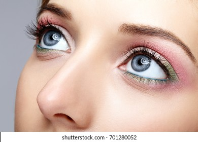 Closeup macro shot of human woman face with pink and green blue eyes makeup
