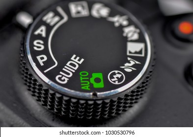 Close-up macro shot of a modern digital SLR camera. Detailed photo of black camera body with buttons to control and switch shooting modes. Selective focus.