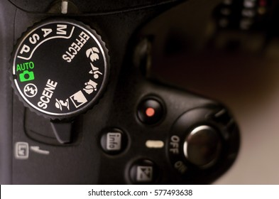 Close-up macro shot of a modern digital SLR camera. Detailed photo of black camera body with buttons to control and switch shooting modes