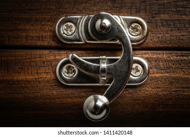A close-up or macro shot of a sliding clasp metal lock on a wooden box.