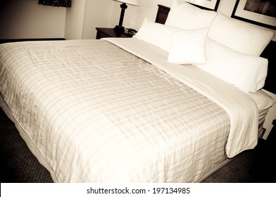 A close-up of a made-up bed in a hotel room.