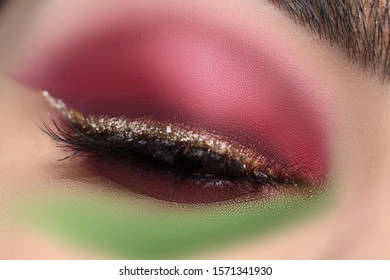 Close-up of magical professional makeup with black lashes smoky eyes and glossy golden eyelid. Pretty woman eye with evening holiday maquillage. Cosmetics and beauty concept