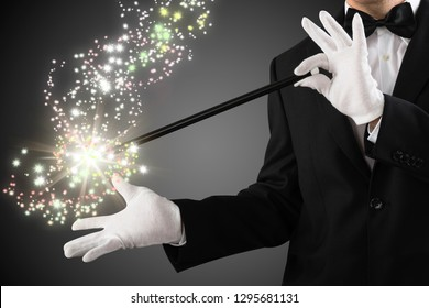 Close-up Of A Magician's Hand Creating Sparkles With Magic Wand On Grey Background