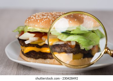 Closeup of magnifying glass examining burger in plate