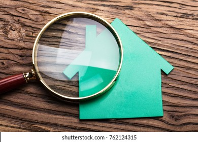 Closeup Of Magnifying Glass And Green Paper House On Wood