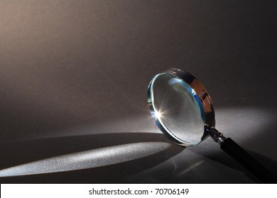 Closeup of magnifying glass standing on dark surface with beam of light