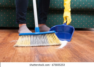 Closeup of maid woman sweeping floor with broom and dustpan at home