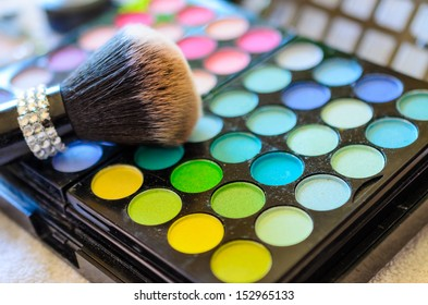 A closeup of makeup brush and color palette