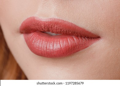 Close-up of make-up on lips, pink, woman smiles. Mouth ajar.