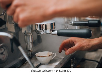 A close-up of making espresso, the coffee is poured into white ceramic cup