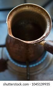 A closeup of making Turkish black coffee in a vintage finjan jezve coffee pot on a gas burner