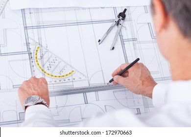 Close-up Of Male Architect Drawing Blueprint In Office