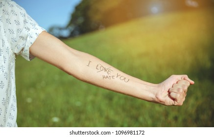 Closeup of male arm with the text -I hate you- and word -love- crossed out in the skin over a sunny nature background