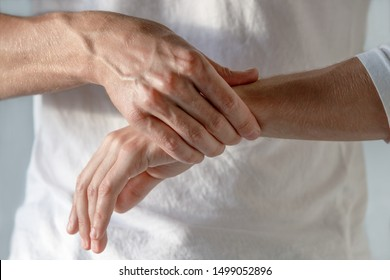 Closeup of male arms holding her painful wrist caused by prolonged work on the computer, laptop. Carpal tunnel syndrome, arthritis, neurological disease concept. Numbness of the hand