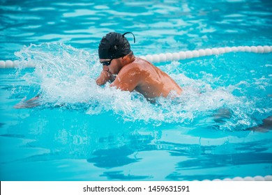 Closeup male athlete swimming breaststroke in pool during Champions.