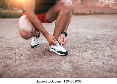 Close-up, a male athlete, tying shoelaces on sneakers. Concept of morning jogging in the city. Tanned leather, smart watch bracelet. Sportswear shorts T-shirt.